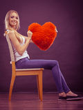 Woman holding heart shaped pillow love symbol Stock Image
