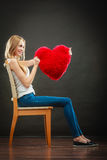 Woman holding heart shaped pillow love symbol. Valentines day love and relationships concept. Blonde long hair young woman holding heart shaped pillow love stock images