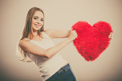 Woman holding heart shaped pillow love symbol. Valentines day love and relationships concept. Blonde long hair young woman holding heart shaped pillow love royalty free stock photos