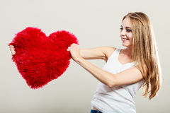 Woman holding heart shaped pillow love symbol Stock Photo