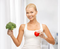 Woman holding heart symbol and broccoli royalty free stock image