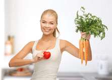 Woman holding heart symbol and carrots Royalty Free Stock Images
