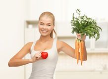 Woman holding heart symbol and carrots Stock Images