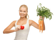 Woman holding heart symbol and carrots Royalty Free Stock Photography