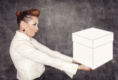 Woman holding heavy box in her hands. On the blackboard background Stock Images