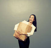 Woman holding heavy paper bag over dark. Laughing woman holding heavy paper bag over dark background Royalty Free Stock Photos