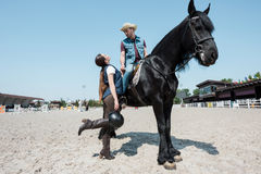Woman holding helmet while handsome man in cowboy hat sitting on horseback Stock Photo