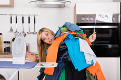 Woman Holding Help Flag Behind Pile Of Clothes Stock Images