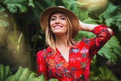 Woman Holding Her Back Head Wearing Brown Hat and Red and Multicolored Floral Button-up Long-sleeved Blouse Royalty Free Stock Photography