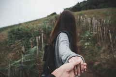 A woman holding her boyfriend`s hand while trekking. In tropical forest Stock Images