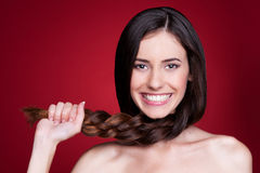 Woman holding her braid and smiling Stock Photo