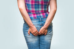 Woman holding her butt isolated on blue background. Diarrhea concept Stock Images