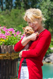 Woman holding her dog. A beautiful blonde woman holding her lapdog Royalty Free Stock Images