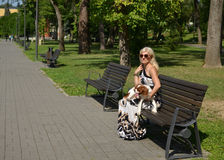 Woman Holding Her Dog on Bench Stock Photography