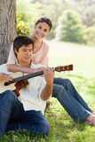 Woman holding her friend as her plays the guitar Stock Photos