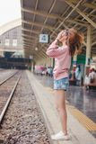 Woman holding her hair standing on the tracks stock image