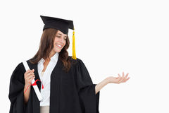 A woman holding her hand out with a degree in her other hand as Royalty Free Stock Photos