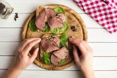 Woman holding in her hands open roast beef sandwich with salad and pepper on rustic wooden plate. Stock Photos