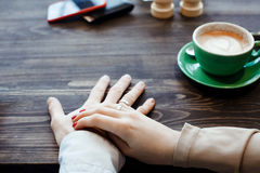 Woman is holding her hands with a ring. Couple drinking coffee at cafe restaurant man and woman with cup hot cappuccino on dating. Concept of male and female Royalty Free Stock Photos