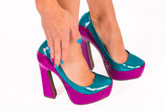 Woman holding her hurting ankle. Glamorous high heel shoes and women holding her hurting ankle Royalty Free Stock Image