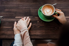 Woman is holding her husband's hand with a ring. The girl holds the hand of her husband, hands close-up cup of coffee and cappuccino, top view on a wooden table stock photos