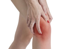 A woman holding her knee in pain, with red highlighted on pain area on a white background Royalty Free Stock Photography