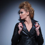 Woman holding her leather jacket's collar and looks to her side. Away from the camera Stock Photography