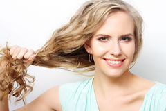 Woman holding her long curly healthy hair Stock Photos