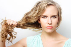 Woman holding her long curly healthy hair. Portrait of a young woman holding her long curly healthy hair Stock Image