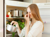 Woman  holding her nose because of bad smell. Long-haired  woman  holding her nose because of bad smell near fridge at home Royalty Free Stock Images