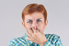 Woman holding her nose with her fingers. Because of bad smell royalty free stock photos