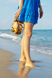 Woman holding her sandals on a beach Stock Images