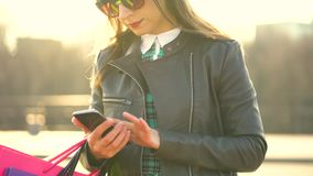Woman holding her shopping bags in her hand and using a smartphone. Let`s go shopping concept stock video footage