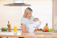 Woman holding her sleeping baby in the kitchen Stock Photo