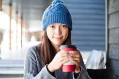 Woman holding her warm coffee. At outdoor coffee shop Royalty Free Stock Image