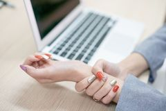 Woman holding her wrist pain from using computer.,Hand pain stock photography