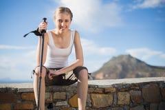 Woman holding hiking stick sitting on wall Stock Image