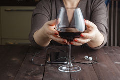 Woman is holding in his hand a glass of alcoholic beverage Royalty Free Stock Images