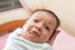 Woman holding a hispanic newborn crying stock photo