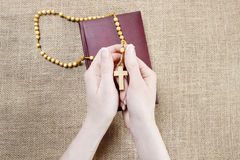 Woman holding Holy Bible and wooden rosary Royalty Free Stock Image