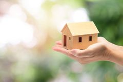 Woman holding home model, loan concept. With nature background royalty free stock images