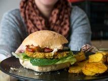 Woman holding a homemade vegan burger royalty free stock photo