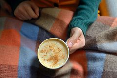 Woman holding hot cup of cappuccino. On blanket Stock Images