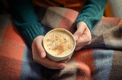 Woman holding hot cup of cappuccino. On blanket Stock Photo