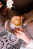 Woman holding hot cup of coffee. A girl in cafe with beige nails is holding a cup with cappuccino with a pattern. Cappuccino Royalty Free Stock Photo