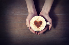 Woman holding hot cup of coffee, with heart shape Royalty Free Stock Images