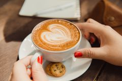 Woman holding hot cup of coffee, with heart shape.  Royalty Free Stock Photography
