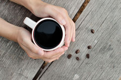 Woman holding hot cup of coffee. On wood table background Royalty Free Stock Image