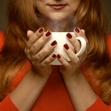 Woman holding hot cup and smiles Stock Photography