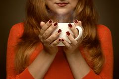 Woman holding hot cup and smiles Royalty Free Stock Photos